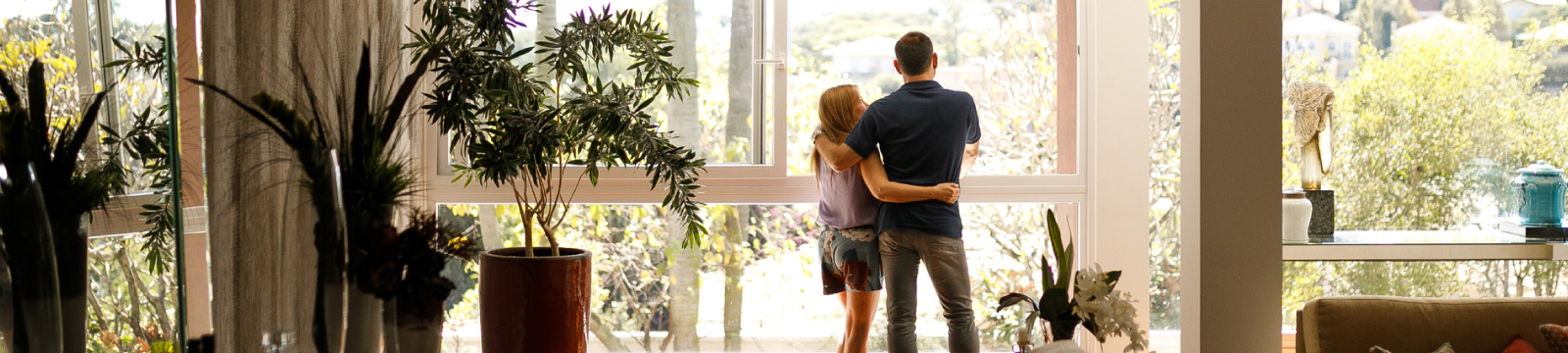 A couple standing in front of window in home